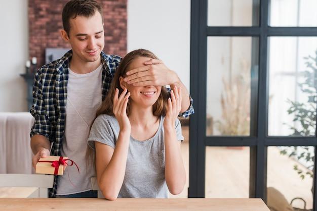 Macho com presente fechando os olhos da mulher Foto gratuita