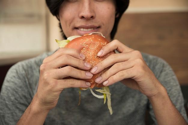 Macho comendo hambúrguer no café Foto gratuita