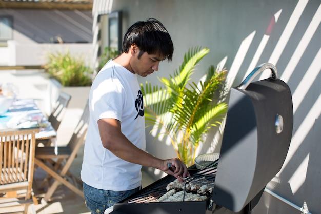 Macho considerável prepara churrasco ao ar livre Foto Premium