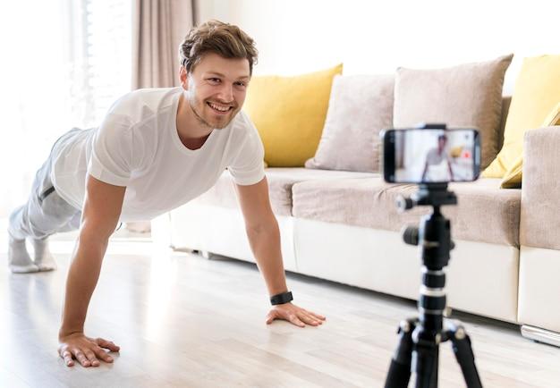 Macho considerável que grava o treinamento pessoal em casa Foto gratuita