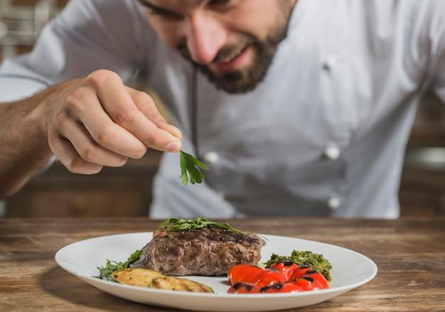 Macho, cozinheiro, garnishing, preparado, prato, ligado, contador cozinha Foto gratuita