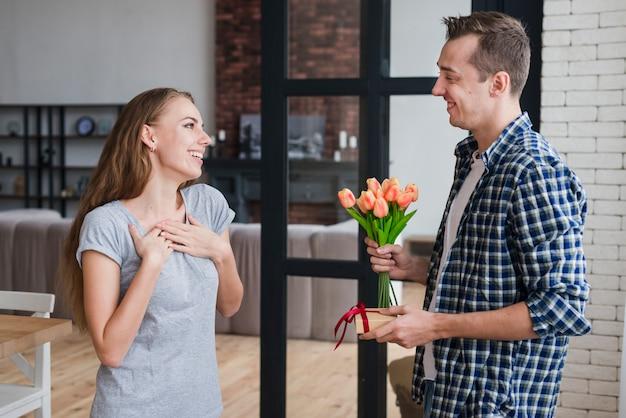 Macho dando flores e presente para mulher Foto gratuita