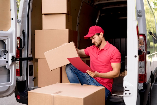 Macho de entrega com lista de pacotes Foto gratuita