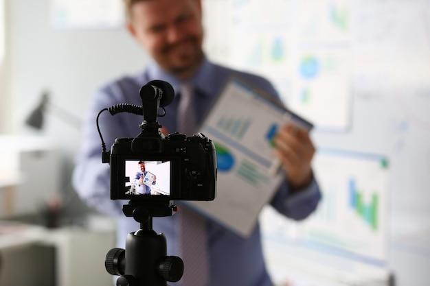 Macho de terno e gravata mostrar estatísticas pad gráfico Foto Premium
