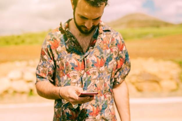 Macho digitando na tela do telefone móvel ao ar livre Foto gratuita