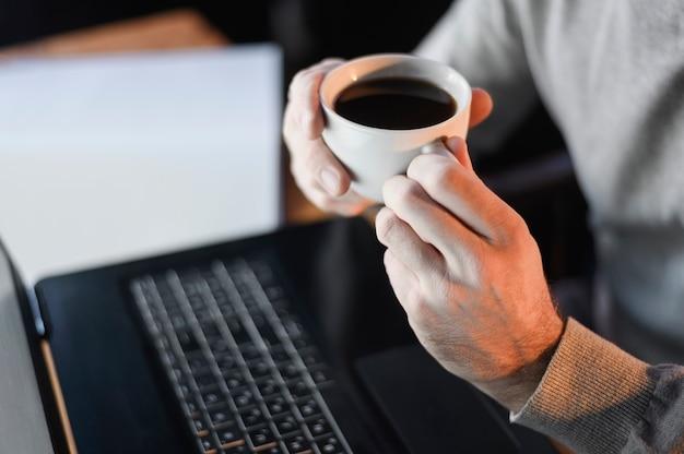 Macho do close-up que guarda a xícara de café Foto gratuita