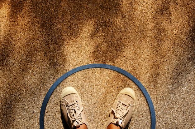 Macho em sapatos de tênis em pé dentro de uma linha de círculo Foto Premium
