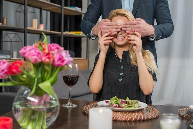 Macho, fechando os olhos para mulher alegre na mesa Foto gratuita
