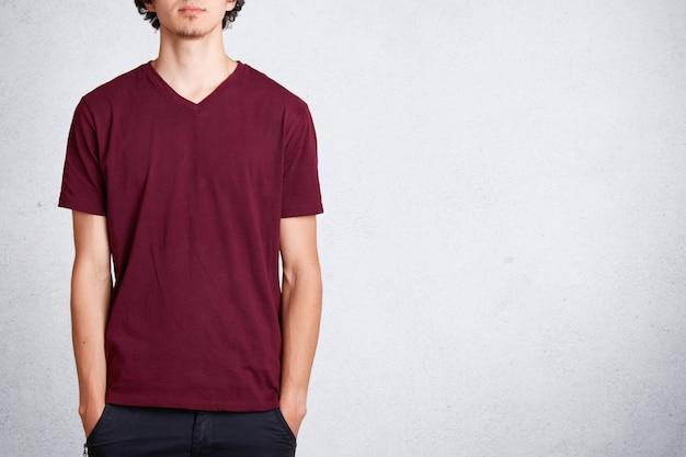 Macho irreconhecível mantém as mãos no bolso, veste camiseta casual com espaço em branco da cópia para seu projeto ou anúncio, fica em branco. conceito de pessoas e roupas Foto Premium