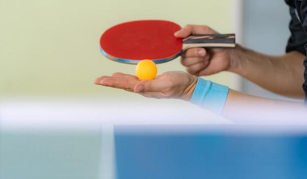 Macho jogando tênis de mesa com raquete e bola em um salão de esporte Foto Premium