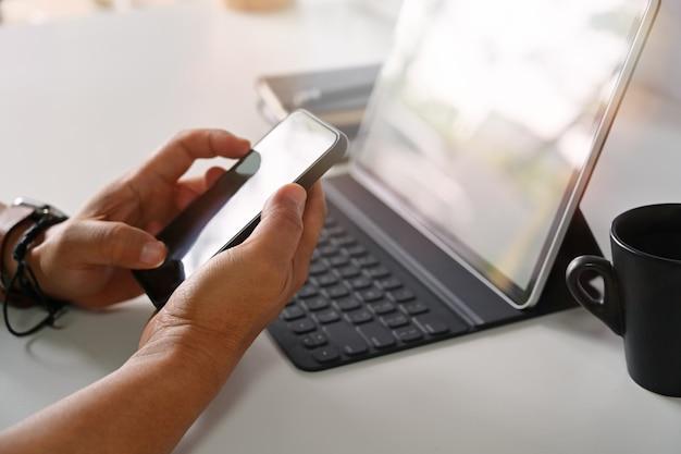 Macho mãos segurando o smartphone móvel no local de trabalho Foto Premium