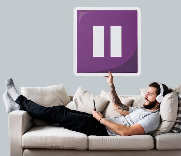 Macho no sofá segurando um ícone de botão de pausa Foto gratuita