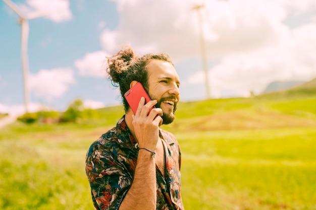 Macho novo de sorriso que fala no telefone no prado Foto gratuita
