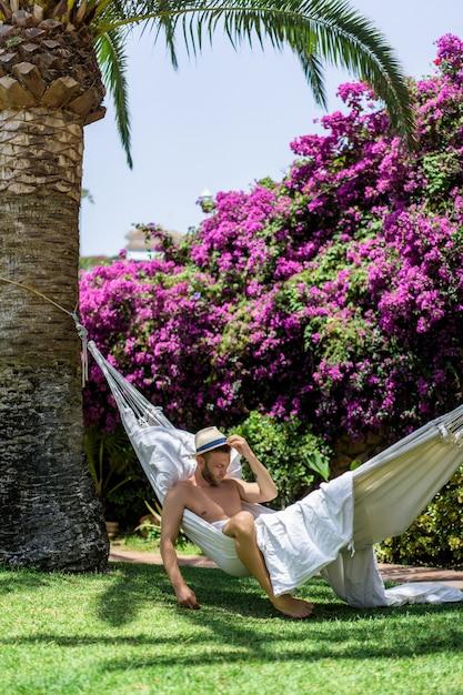 Macho nu que relaxa em uma rede no jardim. Foto gratuita