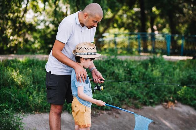Macho pescador ajudando seu filho enquanto pesca Foto gratuita