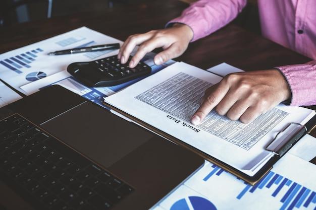 Macho usando computador portátil e calculadora para analisar o mercado de ações Foto Premium