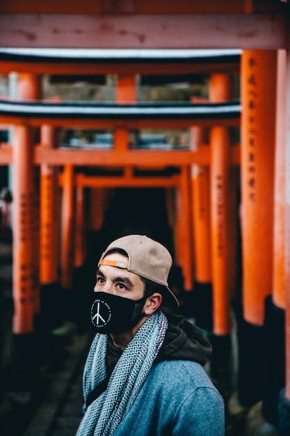 Macho vestindo boné bege, cachecol e pé de máscara preta sobre o fundo desfocado do portão do templo Foto gratuita