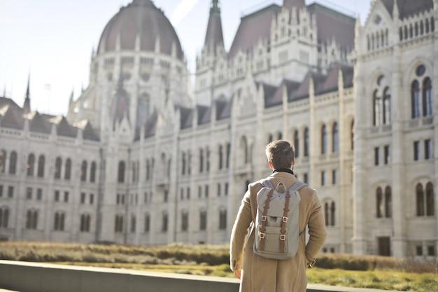 Macho vestindo casaco marrom e mochila perto do edifício do parlamento húngaro em budapeste, hungria Foto gratuita