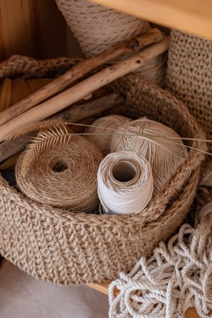 Macramé, algodão e cordas de cânhamo em meadas. crochê, rede de objetos de artesanato em uma cesta de juta Foto Premium
