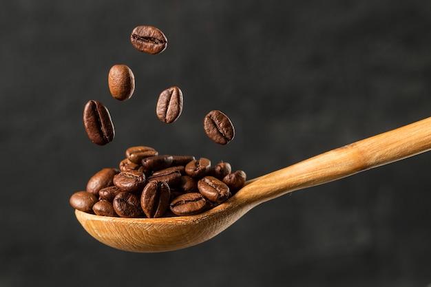 Macro caindo feijão de café sobre fundo cinzento Foto Premium