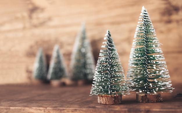 Madeira de árvore de natal na mesa de madeira e parede marrom escuro Foto Premium