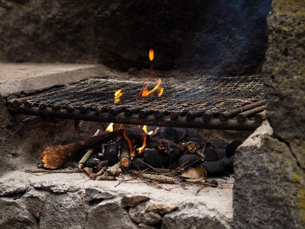 Madeiras ardentes em local de fogueira com fumaça Foto gratuita