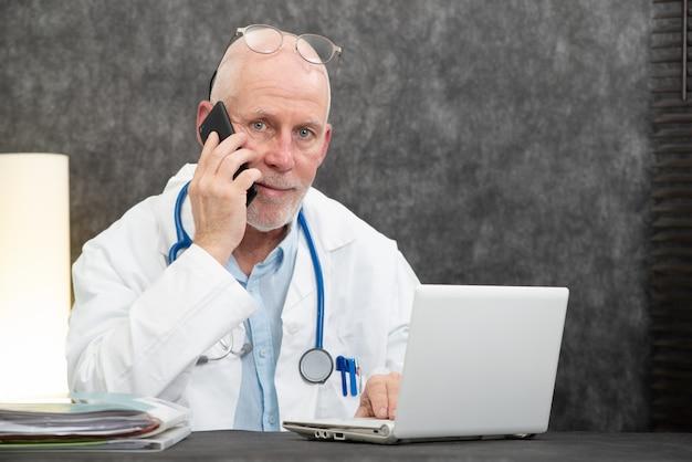 Madura sorridente barbudo médico falando no telefone Foto Premium