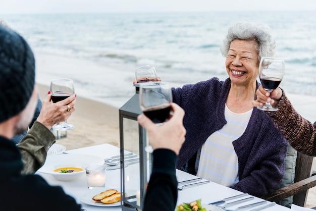 Maduros amigos bebendo vinho na praia Foto Premium