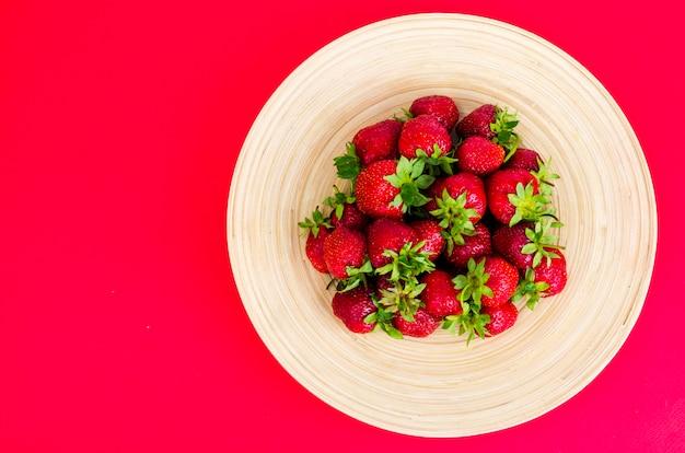 Maduros doces morangos vermelhos no prato de madeira Foto Premium