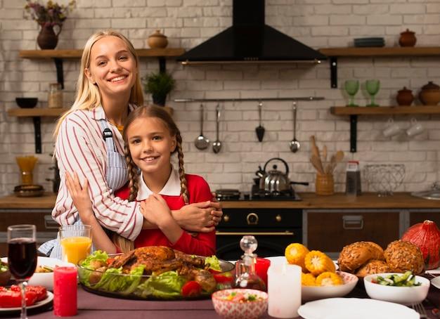 Mãe abraçando a filha na cozinha Foto gratuita