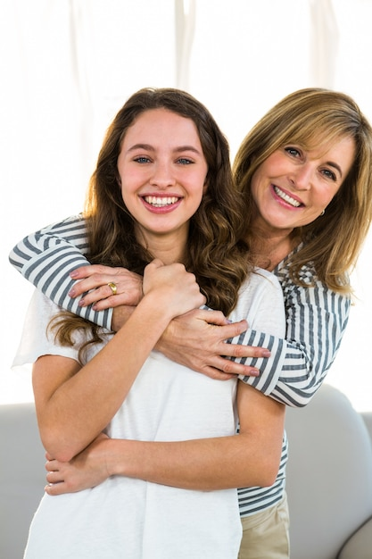 Mãe abraçar a filha dela e sorrindo para a câmera Foto Premium