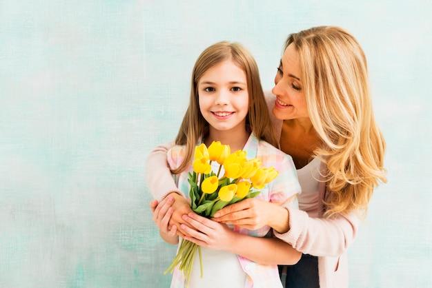 Mãe, abraçar, filha, com, tulips, e, olhar menina Foto gratuita