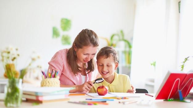Mãe ajuda o filho a fazer a lição de casa. Foto Premium