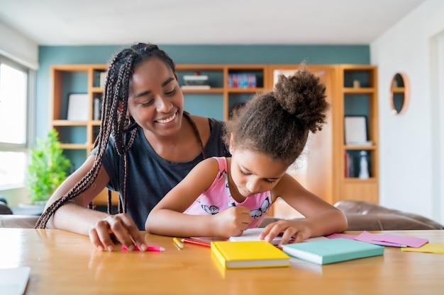 Mãe ajudando e apoiando a filha com o ensino doméstico, enquanto ela fica em casa. novo conceito de estilo de vida normal. Foto gratuita