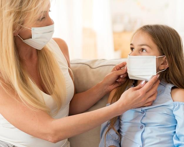 Mãe ajudando filha a colocar máscara médica no rosto Foto Premium