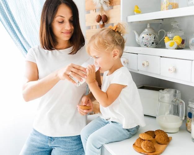 Mãe ajudando menina a beber leite Foto gratuita