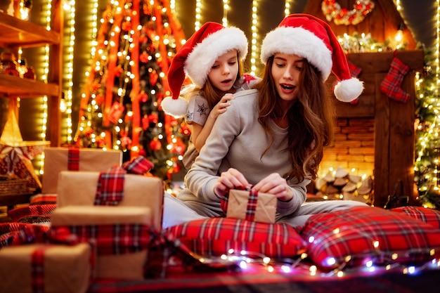 Mãe alegre e sua filha filha troca de presentes. pai e filhos se divertindo perto de árvore dentro de casa. família amorosa com presentes na sala de natal. Foto Premium