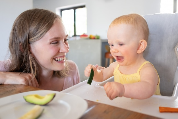 Mãe alegre vendo bebê comendo comida sólida na cadeira alta, rindo e se divertindo. tiro do close up. conceito de cuidado infantil ou nutrição Foto gratuita