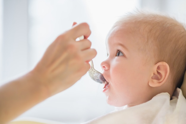 Mãe alimentando seu dia de mingau de peito de bebê Foto Premium