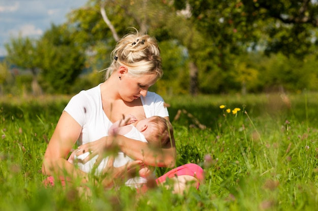 Mãe amamentando bebê no prado Foto Premium