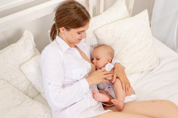 Mãe amamentar bebê 6 meses de idade, deitado em uma cama branca, alimentação do bebê Foto Premium