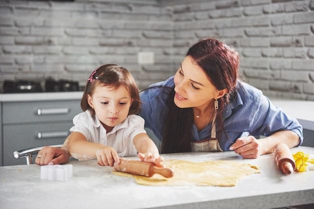 Mãe amando o forno para a filha do biscoito. Foto gratuita