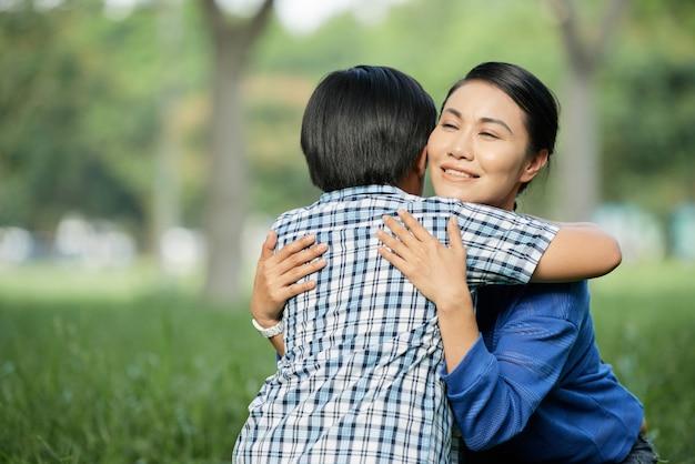 Mãe amorosa, abraçando o filho pequeno Foto gratuita