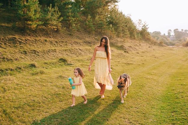Mãe anda com sua filhinha e seu cachorro Foto Premium