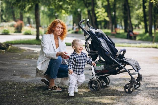 Mãe andando no parque com seu filho pequeno Foto gratuita