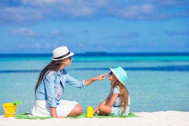 Mãe, aplicando, creme proteção sol, para, dela, filha, em, praia tropical Foto Premium