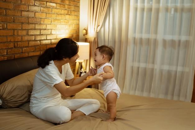 Mãe asiática brincando com seu bebê na cama Foto Premium