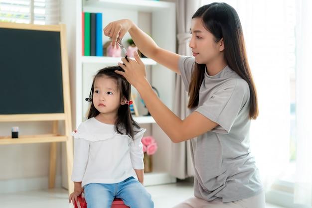 Mãe asiática cortando cabelo para a filha na sala de estar em casa enquanto fica em casa a salvo do covid-19 coronavirus durante o bloqueio. auto-quarentena e conceito de distanciamento social. Foto Premium