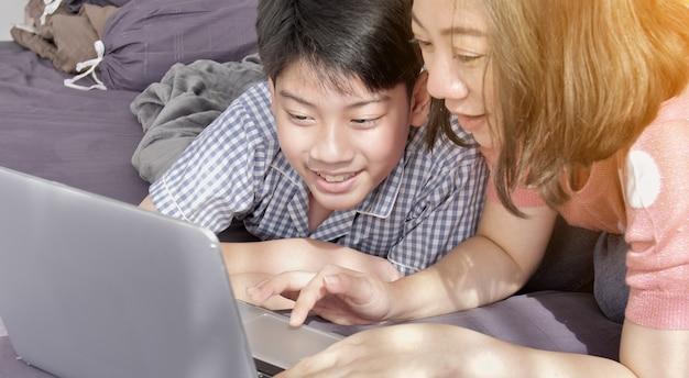 Mãe asiática e filho da família que olham no computador portátil. Foto Premium