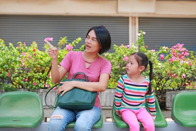 Mãe asiática e sua filha sentada na estação de ônibus Foto Premium